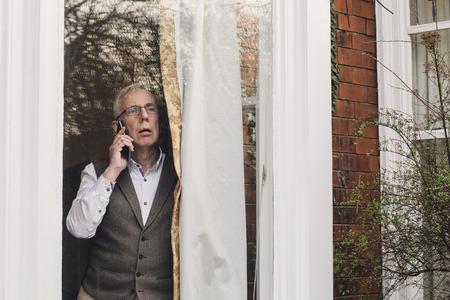 시니어 남자가 전화로 경찰에게 이웃 범죄를 신고합니다. 그는 창밖을보고 있습니다.