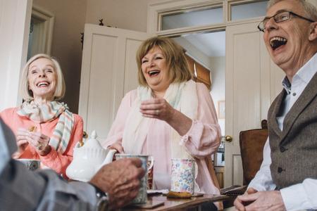노인 그룹 집에서 차와 비스킷을 즐기고있다.