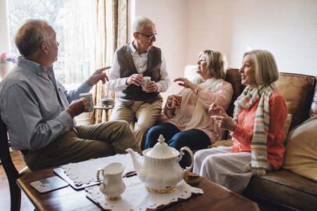Group of seniors are sitting in the living room of a home together, enjoying a pot of tea and a chit-chat together.