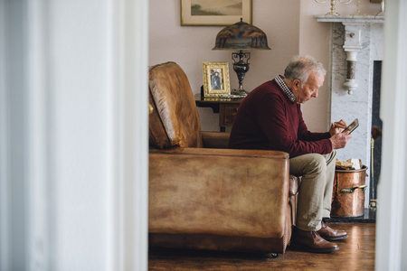 Senior man is sitting in an armchair in the living room of his home, holding and looking at an old photo with a sad expression. Stock Photo