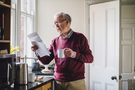 Senior man is standing in the kitchen of his home with bills in one hand and a cup of tea in the other. He has a worried expression on his face. Stock Photo - 78146942