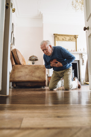 palpitations: Senior man having a heart attack in his home. Stock Photo