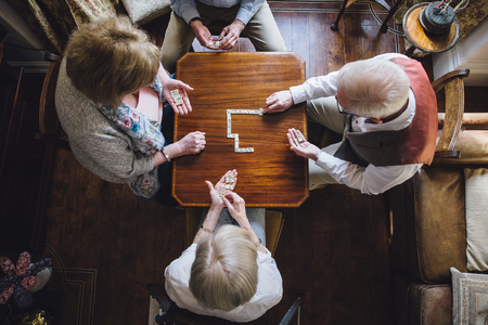 Aerial shot of four senior adults playing dominoes on a table in the nursing home. Stock Photo
