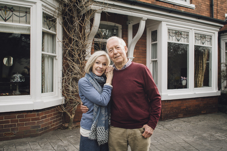 Senior couple are smiling for the camera while standing in front of their home. Reklamní fotografie