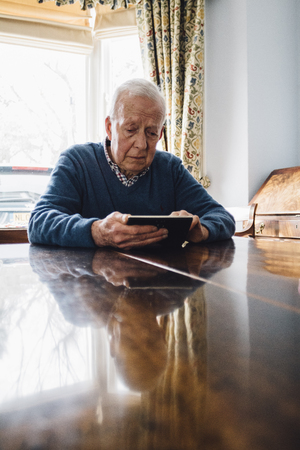 Senior man is sitting at his kitchen table in his home, looking sadly at a picture frame in his hands. Stock Photo