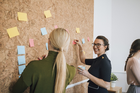 Two women are at work in an office. They are standing at a cork board and are having a discussion as they pin things up. Stock Photo