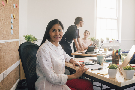 Portrait of a female employee in her workplace. She is sitting at her desk and is smiling at the camera. Stock Photo