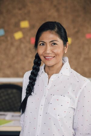 smartly: Portrait of a beautiful woman in her workplace. She is standing in front of a corkboard and is smartly dressed, smiling for the camera.