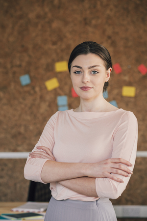 smartly: Portrait of a female office worker. She is standing in front of a cork board, smartly dressed with her arms folded and is smiling for the camera. Stock Photo