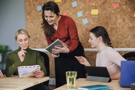 女性は、オフィスで一緒に働いています。彼らは、彼らはデジタル タブレットを使用すると話しています。 写真素材 - 78800319