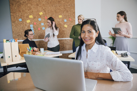 Beautiful woman is smiling for the camera while sitting at her desk in her workplace. There are women working in the background.
