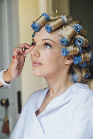 Beautiful bride is having a makeover on her wedding day. She has rollers in her hair and someone is applying product to her face. Banco de Imagens