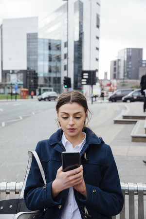 Young woman is standing in the city looking at a smart phone in her hands.  Stock Photo