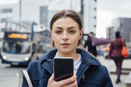 Portrait of a young woman with a smart phone. She is standing in the city and is looking at the camera.
