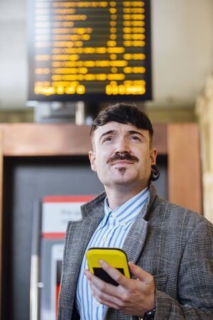 Young businessman is using his smart phone to check for his train time on the departure board.