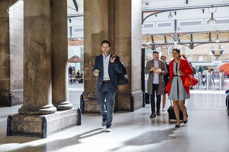 Businesspeople are leaving the train station to commute to work.