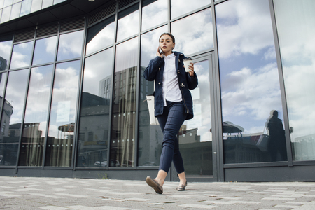 Young businesswoman is leaving her office building with a cup of tea. She is talking on the phone to someone as she walks. Stock Photo