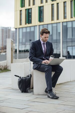Businessman is working in the city. He is using a laptop and drinking a coffee.