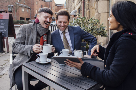 Happy couple are sitting with a financial advisor at a cafe. She is showing them a digital tablet with information and they are laughing while drinking tea.