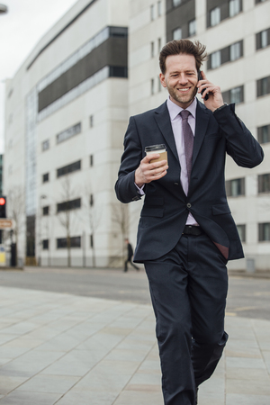 Businessman is walking to work in the city. He is holding a coffee cup and is talking on the phone.
