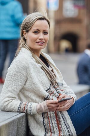 Beautiful woman is sitting in the city with a smart phone in her hands. She is smiling at the camera.