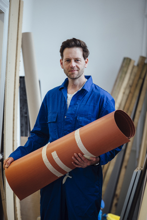 vision repair: Portrait of a male construction worker with a roll of flooring in his hands.