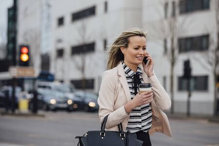 Businesswoman is walking to work in the city. She is holding a coffee cup and is talking on the phone. Stock Photo