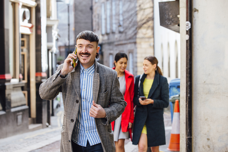 Businessman is walking through the city to go to work. He is well dressed and is talking on the phone, while two women can be seen in the background walking together while lookin at a smart phone. Stock Photo