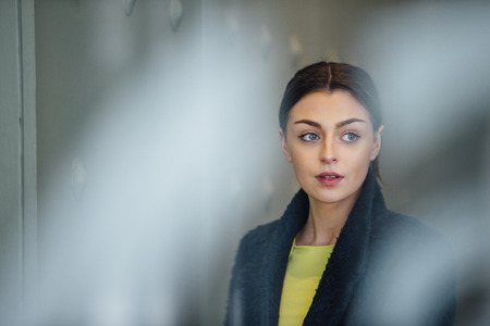 Businesswoman is standing in her workplace, looking out of her office window.