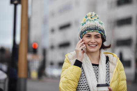 defocussed: Woman is walking in the city with a coffee cup while talking on the phone. Stock Photo