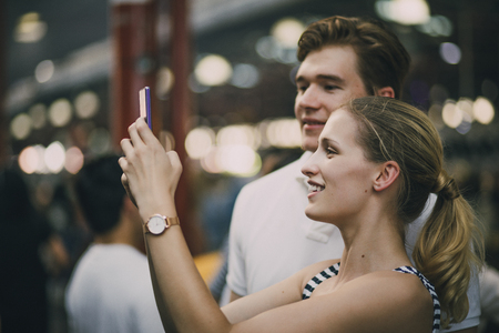 Young couple are taking tourist photos in Queen Victoria market, Australia.