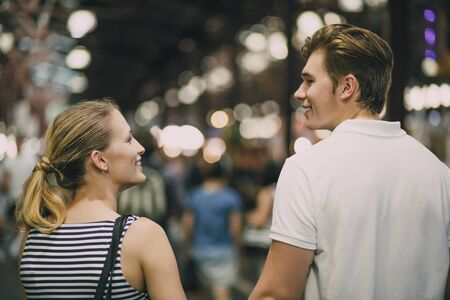 Happy couple are talking as they walk together through Queen Victoria Market, Australia.