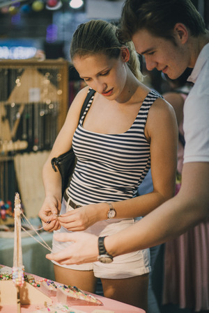 tent city: Young couple are looking at a jewellery stall in Queen Victoria Market, Australia.
