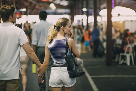 Young couple are exploring Queen Victoria Market in Australia. They are holding hands and the woman is looking out oft he frame to something she is tempted to buy. Stock Photo