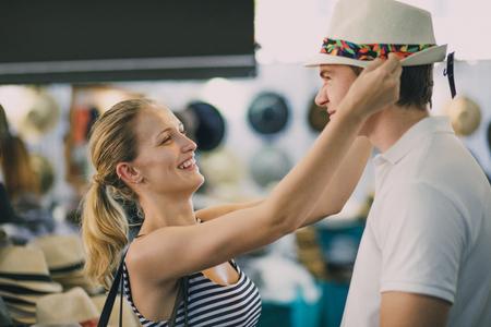 Het gelukkige jonge paar onderzoekt Koningin Victoria Market in Australië. De vrouw heeft een zomerhoedje van een kind gevonden en probeert het op het hoofd van haar vriend te persen, terwijl hij een gezicht trekt.