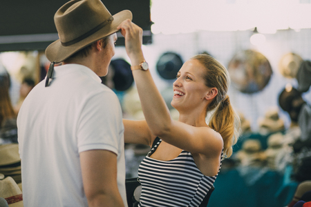 Young couple are exploring Queen Victoria Market in Australia. The woman is putting a hat on her boyfriend in a market stall. Stock Photo