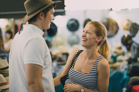 Young couple are exploring Queen Victoria Market in Australia. The woman has put a hat on her boyfriend in a market stall.
