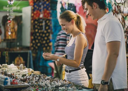 Young couple are looking at a jewellery stall in Queen Victoria Market, Australia.