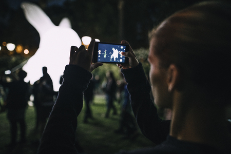 Young woman is taking photos on her smartphone of the displays at White Night in Melbourne, Australia. Banco de Imagens