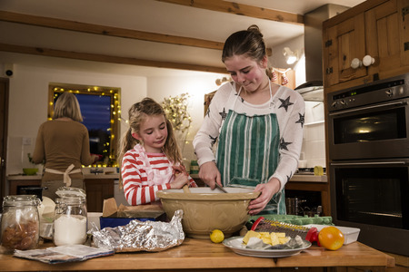 grandkids: Two sisters are baking cakes in the kitchen with their grandmother. The girls are mixing ingredients. Stock Photo