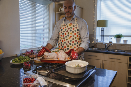 Mature man is preparing the Christmas dinner in the kitchen of his home. He is about to put the turkey in the oven. Imagens