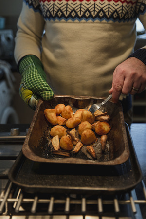 Close up shot of roast potatoes and parsnips in a tray. A man is holding it and flipping the vegetables over. Stock Photo