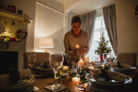 Happy mother is setting the table for Christmas dinner with her family.  She is lighting candles.