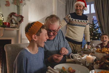 Little boy is laughing as his grandfather tells him a joke from a christmas cracker at the dinner table.