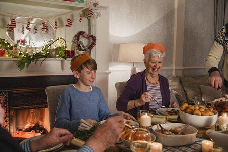 家族のクリスマス ディナーの視点ショット。みんなは、食品をその板を充填です。