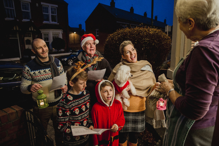 Three generation family are doing door-to-door carol singing. There is a senior woman at the door, appreciating their singing. Zdjęcie Seryjne - 82734826