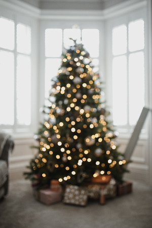 Defocussed christmas tree in a living room with presents underneath it.