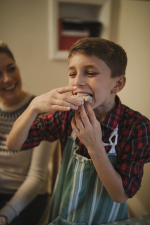 Little boy is tucking in to a homemade christmas biscuit.