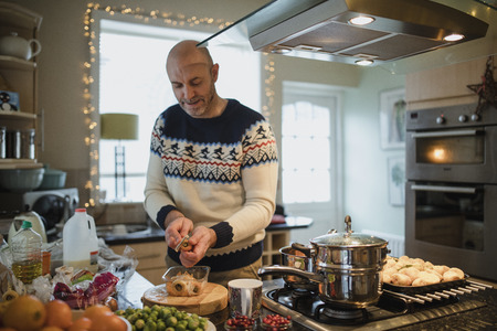 한 성숙한 남자가 그의 집 부엌에서 크리스마스 저녁을 준비하고 있습니다. 그는 당근과 파스 닙을 벗겨 내고있다.