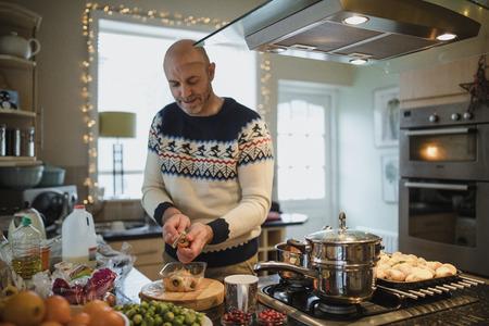 Um homem maduro está preparando um jantar de Natal na cozinha de sua casa. Ele está descascando cenouras e nabos. Foto de archivo - 82088504